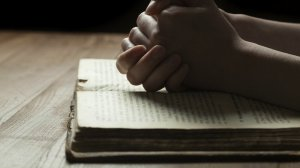 Praying Hands over Scripture
