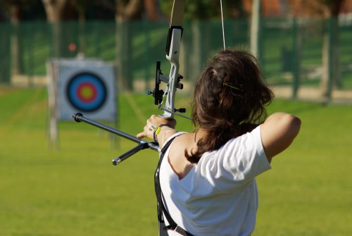 Archery: woman aiming at target